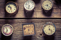 Aged wooden wall with clocks. Closeup of aged wooden wall with clocks stock photography