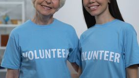 Aged and young women volunteers looking to cam and smiling, charity organization stock video