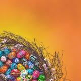 Agencement de panier d'oeufs de pâques sur l'orange Photographie stock libre de droits