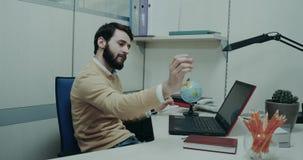 Agencja podróży, charyzmatyczny faktorski obsiadanie na jego biurku i bawić się z geograficznym clipart ma, uśmiechniętego i szcz zbiory wideo