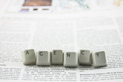 Agency spelled and newspaper. Agency spelled word on newspaper royalty free stock photography