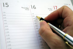 Agenda. A female hand writing the day plan in a diary Royalty Free Stock Image