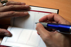 Agenda. Female hand holding a pen to fill the Agenda Royalty Free Stock Image