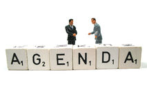 Agenda. Two people having a meeting behind the word agenda royalty free stock image