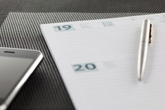 Agenda. Close-up on an open agenda and modern mobile phone. Blank page. Shallow depth of field royalty free stock images