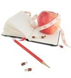 Agenda avec la pomme et pilules pour suivre un régime pertinent photographie stock