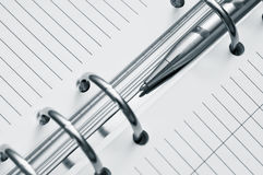 Agenda and ball pen. In grey light royalty free stock photo