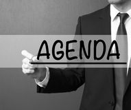 Agenda. Businessman in a suit with a marker writing on visual sc Stock Photography