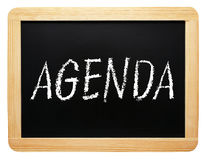 Agenda - chalkboard with text on white background. Agenda - wooden chalkboard with text on white background stock image