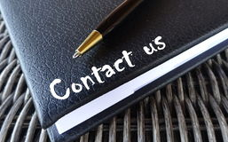 Contact us concept with agenda and pen. Royalty Free Stock Images