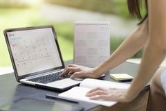 Agenda e programação do planeamento da mulher usando o planejador de evento do calendário fotografia de stock royalty free