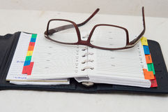Agenda and glasses. A pair of glasses placed in a diary Stock Photo