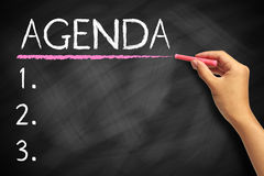 Agenda. Hand with red chalk writing Agenda Concept on chalkboard Royalty Free Stock Image