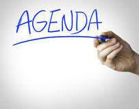 Agenda hand writing on blue marker on transparent wipe board.  stock photos