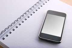 Agenda and mobile phone. Mobile phone and spirals with a white agenda Royalty Free Stock Images