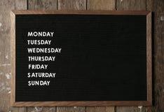 Agenda na czerni desce na drewnianej ścianie Zdjęcia Stock