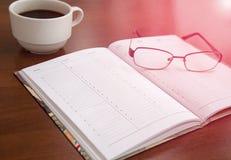 Agenda op een houten lijst, naast glazen en een kop van koffie Stock Foto's