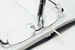 Agenda ouvert d'affaires avec le crayon lecteur et les glaces Photo libre de droits