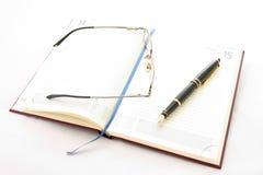 Agenda, pen en glazen stock afbeeldingen