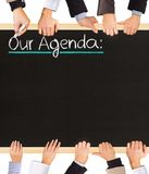 Agenda. Photo of business hands holding blackboard and writing Our Agenda stock photos