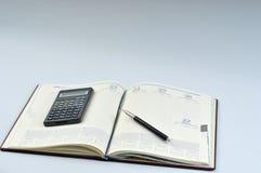 Agenda, pluma y calculadora Imagen de archivo