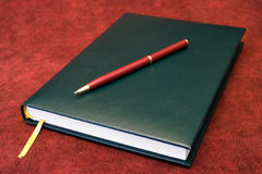 Agenda and red pen. A green agenda under a red pen, useful in business designs royalty free stock photo