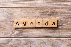 AGENDA word written on wood block. ADAPT text on wooden table for your desing, concept royalty free stock photos