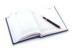 Agenda y pluma en el fondo blanco imagen de archivo libre de regalías