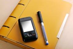Agenda y teléfono móvil Foto de archivo libre de regalías