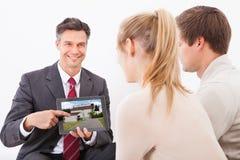 Agent avec le PC de comprimé montrant la maison aux couples Photo stock