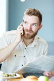 Agent. Calling businessman with newspaper having lunch in cafe Royalty Free Stock Photo
