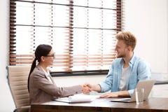 Agent d'assurance femelle serrant la main au client images stock