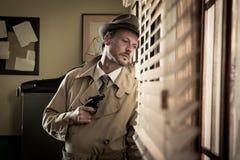 Agent d'espion jetant un coup d'oeil d'une fenêtre Photographie stock libre de droits