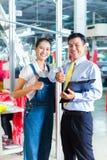 Agent de maîtrise asiatique dans l'usine de textile donnant la formation Image stock