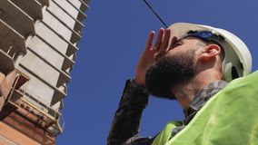 Agent de maîtrise de construction avec une barbe et une moustache portant un casque dans la perspective d'une maison en construct banque de vidéos