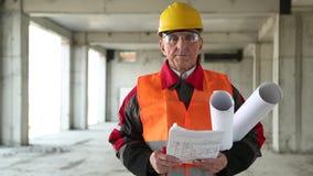Agent de maîtrise général avec des dessins de bâtiment au site de projet banque de vidéos
