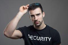 Agent de sécurité dur enlevant des lunettes de soleil avec le regard fixe intense à l'appareil-photo Photos libres de droits