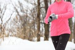Agent die smartwatch jogging gebruikt die in de winter loopt stock afbeeldingen