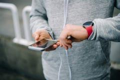 Agent die sportief slim horloge en smartphone voor opleiding gebruiken stock fotografie