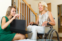 Agent and disabled woman talking. Positive insurance agent and smiling disabled women on chair indoor Royalty Free Stock Photos