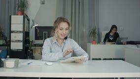 Agent focalisé de centre d'appels utilisant le comprimé numérique sur son lieu de travail image libre de droits
