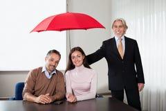 Agent fournissant le cache d'assurance à un jeune couple Photo stock