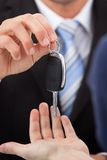 Agent giving car key to man Stock Photo