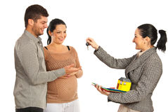 Agent giving house keys to couple Stock Images