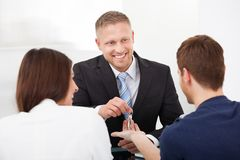 Agent Giving House Keys To Couple. Happy estate agent giving house keys to young couple in office Royalty Free Stock Photos