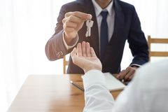 Agent giving keys of new house with customer stock images