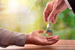 Agent giving the keys to the buyer of a house. With house on nature background royalty free stock images