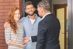 Agent giving keys to smiling couple Royalty Free Stock Photo