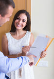 Agent greeting householder and bagging subscriptions in hall Stock Image
