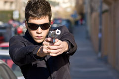 Agent with gun. Agent aiming with gun in the middle of the street Royalty Free Stock Images